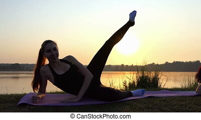 Pregnant Woman Lies on a Mat, Raises Her Leg, on a Lake Bank at Sunset