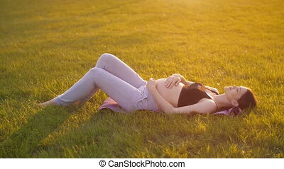 Pregnant Woman Lies on the Grass