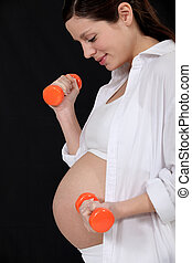 Pregnant woman lifting dumbbells