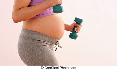Pregnant woman lifting dumbbells