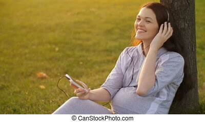Pregnant Woman listening to music on nature