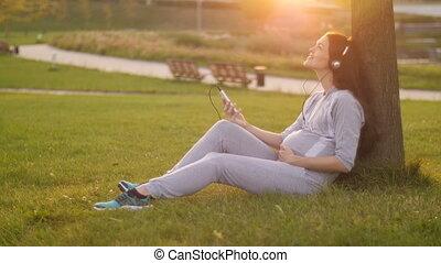 Pregnant Woman listening under tree