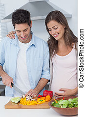 Pregnant woman looking at husband cutting vegetables