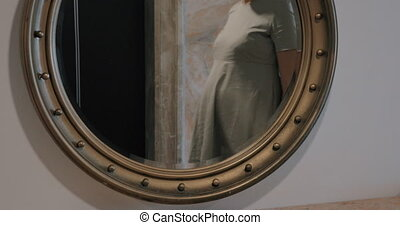 Pregnant woman looking at mirror and stroking belly
