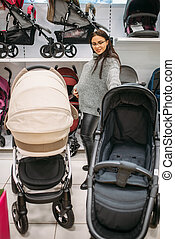 Pregnant woman looking for pushchair in store of goods for...