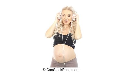 Pregnant woman lsten to music with baby inside stomach by headphones, white