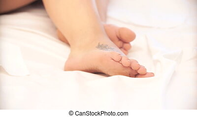pregnant woman lying on the bed. focus on the legs and blur on the face