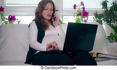 Pregnant woman making business call and working with computer at home