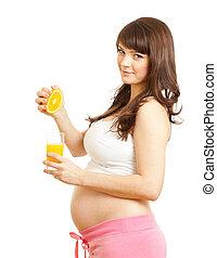 pregnant woman making fresh orange juice