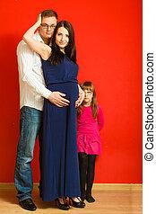 Pregnant woman, man and daughter posing.