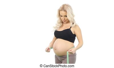 Pregnant woman measures her tummy by tape measure, white