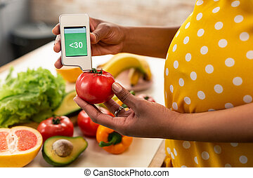 Pregnant woman measuring the level of nitrates in tomato.