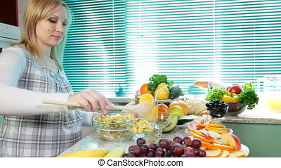 woman mixing fruit salad