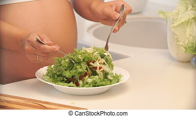 pregnant woman mixing salad in a bowl in the kitchen.