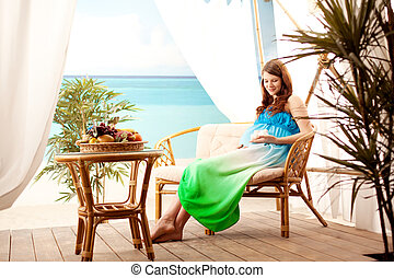 Pregnant woman on the beach in bungalow