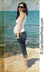 pregnant woman on the beach. Photo in old image style.