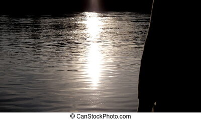Pregnant woman pats her belly on background sunset on river