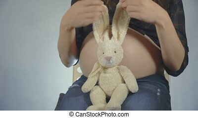 Pregnant woman playing with a bunny plush toy posing