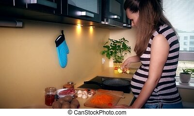 Pregnant woman pour sunflower oil into cooking pan and put shredder carrots