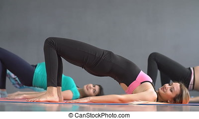 Pregnant woman practicing yoga along with a fitness instructor in the gym