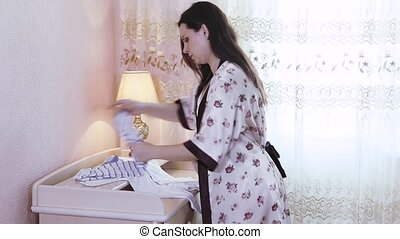Pregnant woman prepares the baby things