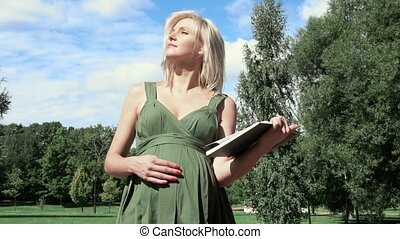 Pregnant woman reading a book in the park