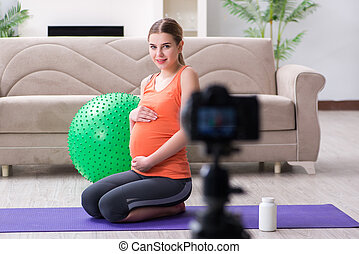 Pregnant woman recording video for blog and vlog