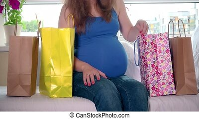 Pregnant woman sitting between shopping bags and stroking her big belly