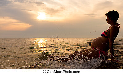 Pregnant woman sitting in the shallow water