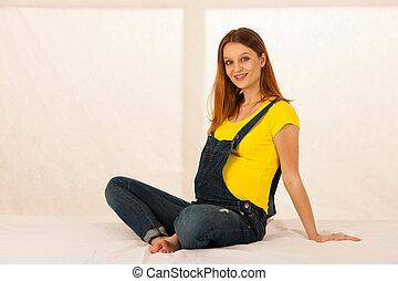 Pregnant woman sitting on bed restnig