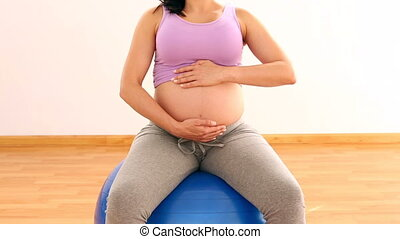 Pregnant woman sitting on blue ball