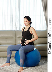 Pregnant woman sitting on fitness ball