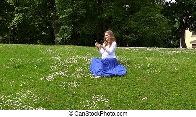 pregnant woman sitting on meadow and picking daisy flowers