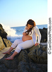 Pregnant woman sitting on rocks at the beach