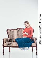 Pregnant woman sitting on the couch in a white background