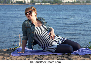 Pregnant woman sitting on the river coast