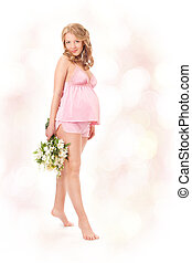 Pregnant woman smiling, looking at camera, holding flowers.