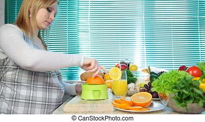 Pregnant woman squeezing orange