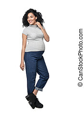 Pregnant woman standing in full length smiling looking to...
