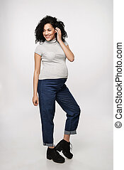 Pregnant woman standing in full length smiling posing,...