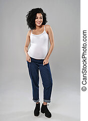 Pregnant woman standing in full length smiling looking down,...