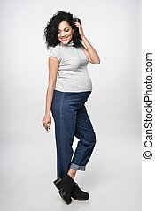 Pregnant woman standing in full length smiling posing, over...