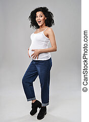 Pregnant woman standing in full length with expression of...