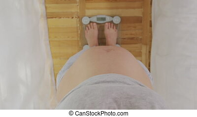 Pregnant woman standing on scale, closeup, 6k