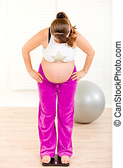 Pregnant woman standing on weight scale at living room