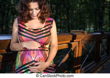 Pregnant woman stands on bridge.
