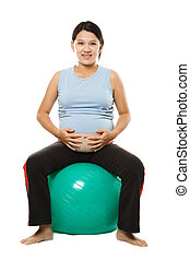 Pregnant woman - A pregnant woman sitting on an exercise...
