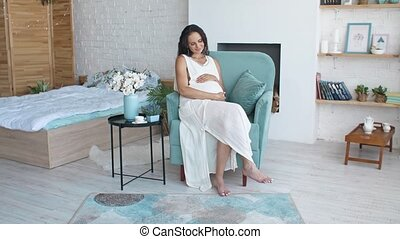 Beautiful pregnant woman on thr chair