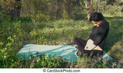 Pregnant woman stroking her baby belly sitting on grass