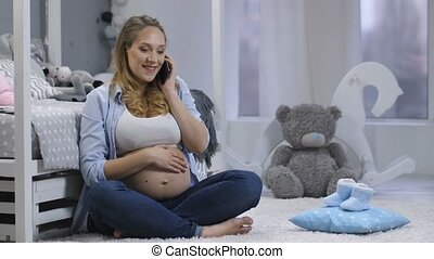 Pregnant woman talking on mobile phone - Young happy...